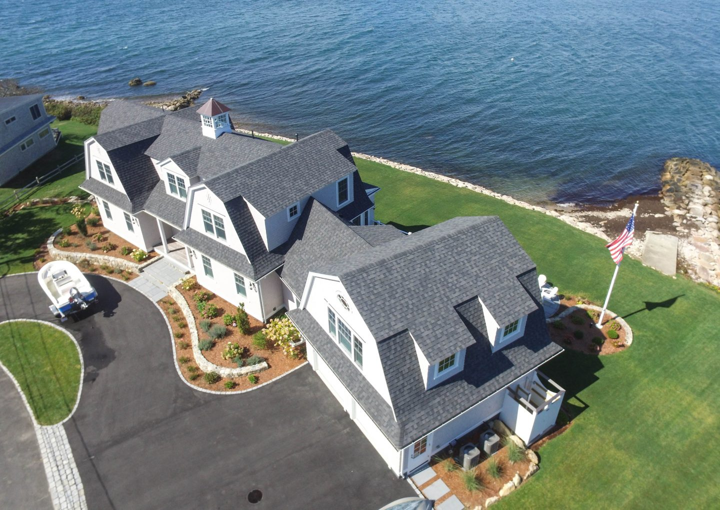 Waterfront home drone picture showing driveway and extensive gardens