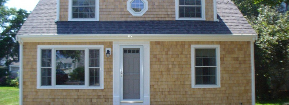 A small Cape Cod home with brand new cedar siding and white painted trim