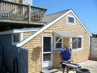A Ryan Construction contractor fixing up the siding and trim of a beach shack on Ridgevale Beach in Harwich, MA
