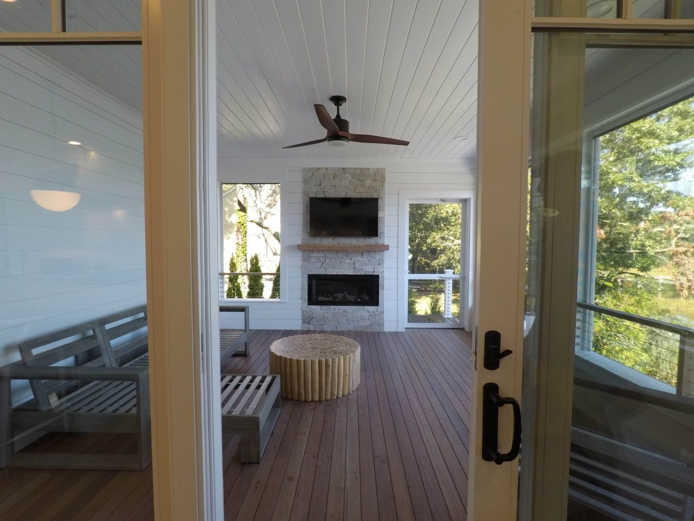 A screened-in outdoor deck becoms a four-season room with a couch, fireplace and TV
