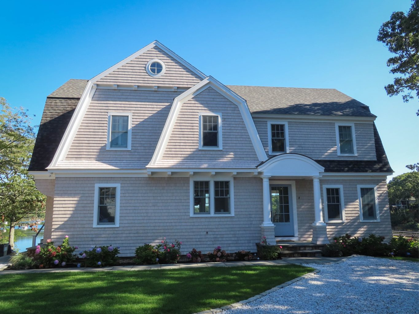 Large home with gambrel style roof and a stone driveway.