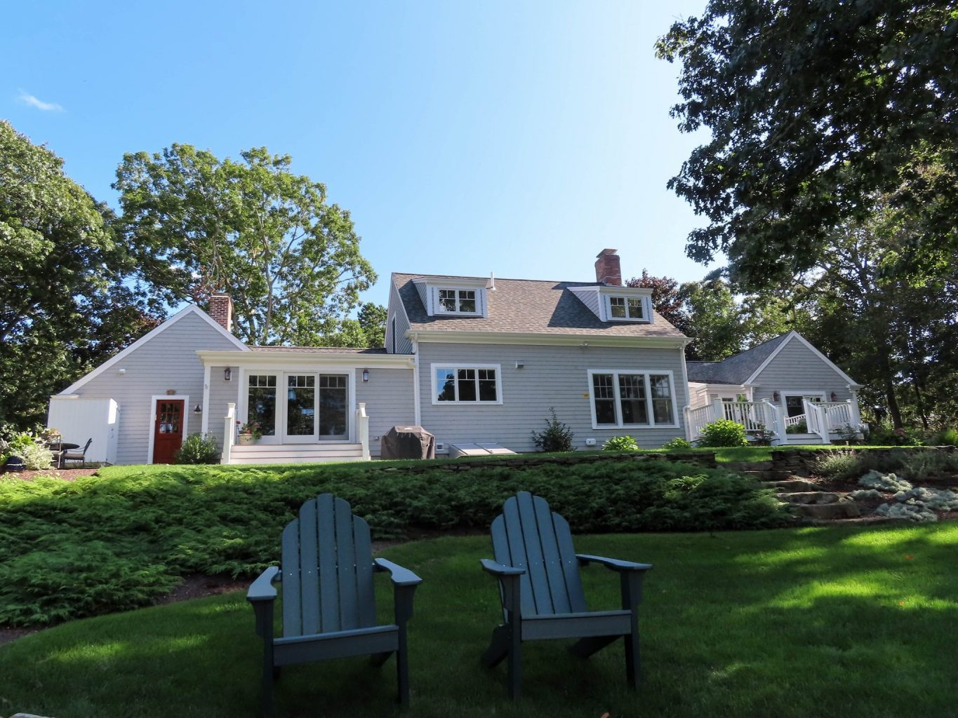 Back yard of a sprawling home with 2 adirondack chairs