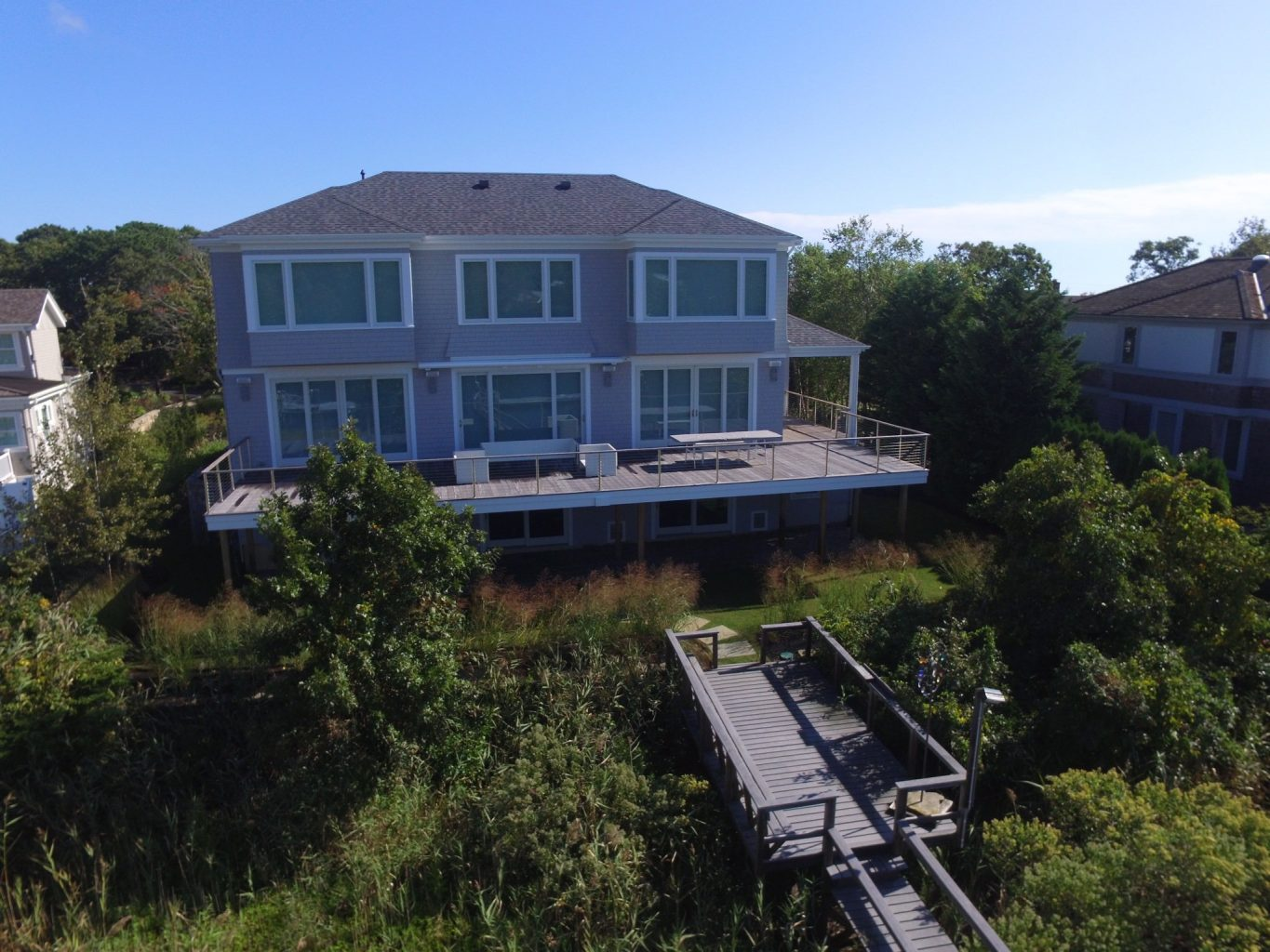 Large home with a wrap around deck and a dock