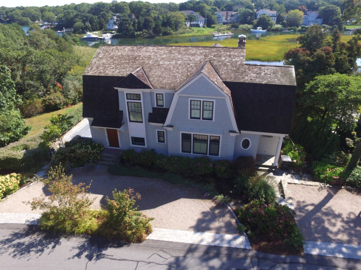 Arial view of a large home with gambrel style roof and a pond in the background
