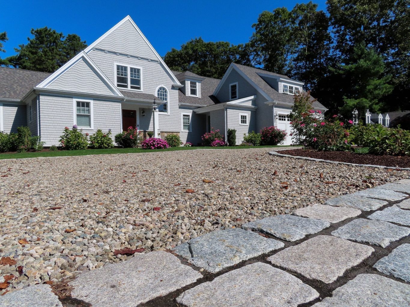New peastone driveway with stone apron leads up to a Cape Cod style home with two levels and an addition