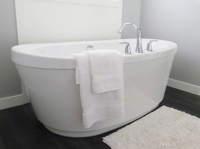 An inviting modern white free standing bathtub in a remodeled bathroom with a wood floor and bathmat