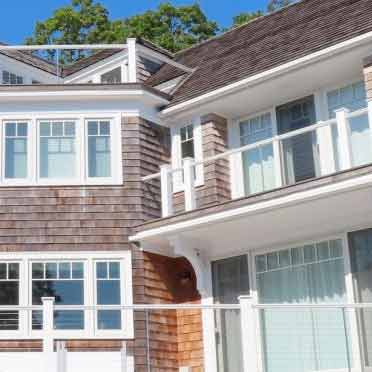 A multilevel house with railings, old shingles and brand new windows and doors including a sliding patio door.