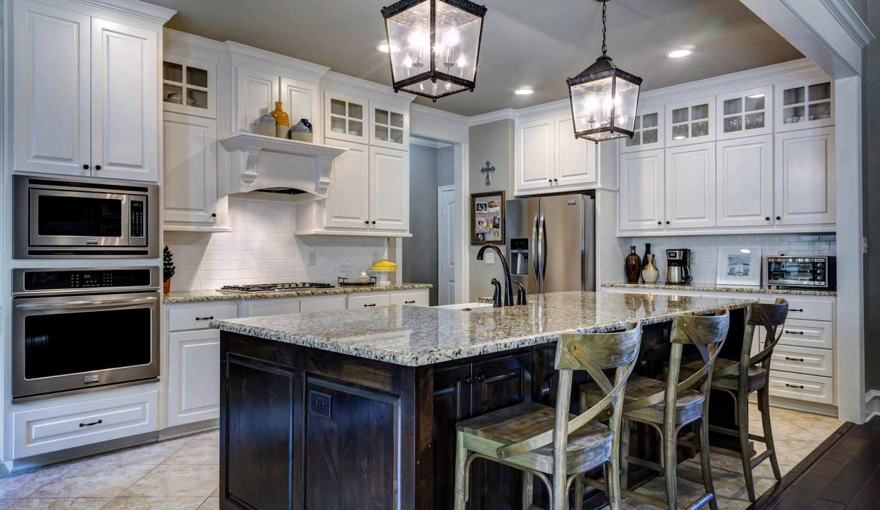 A new kitchen with island and marble countertops, barstools and fresh lighting and a built-in oven